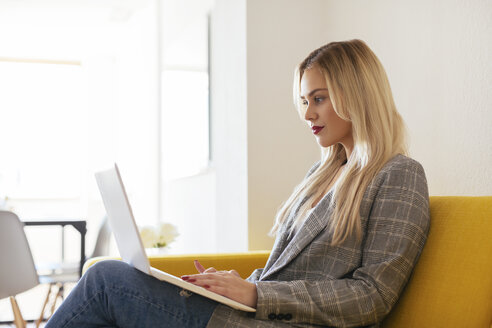 Businesswoman sitting on yellow couch, using laptop - EBSF02344
