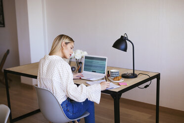 Blond businesswoman sitting at desk, working - EBSF02356