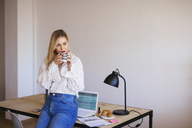 Young woman working in office, taking a break, drinking coffee - EBSF02365