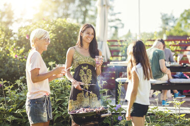 Happy women preparing food on barbecue while looking at girl in back yard - MASF02377