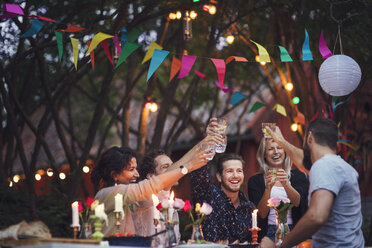 Happy friends toasting drinks while enjoying at garden party - MASF02389