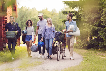 Happy friends with bicycle and luggage walking on pathway by cottage - MASF02395