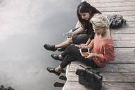 High angle view of happy businesswomen using smart phone while sitting on pier by lake - MASF02410