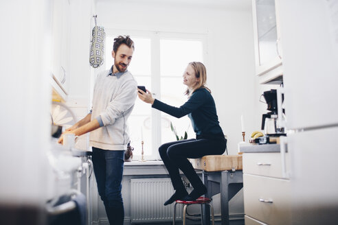 Happy woman showing mobile phone to man in kitchen at home - MASF02416
