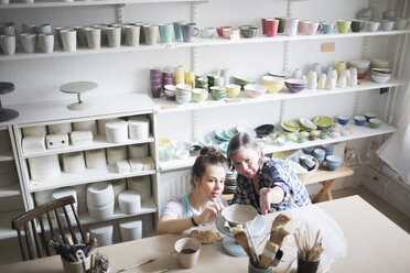 High angle view of mature female potter assisting young craftsperson in molding clay at workshop - MASF02419