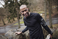 Happy male athlete listening music while exercising by stone wall in forest - MASF02425