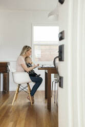Full length side view of woman with daughter using laptop at home - MASF02455