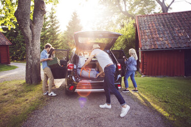 Full length of friends loading luggage into car on road during sunny day - MASF02464