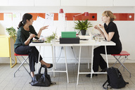Full length of businesswomen talking while having lunch at table in office - MASF02491