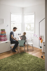 Father playing with daughter at small dining table in playroom - MASF02500