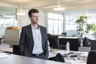 Portrait of a successful businessman standing in office, looking serious - DIGF03902