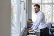 Portrait of a successful businessman stansing in office, looking out of window - DIGF03905