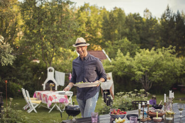 Cheerful man carrying plates by dining table in back yard during garden party - MASF02507