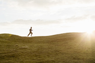 Distant view of man jogging on grassy hill against sky during summer - MASF02516