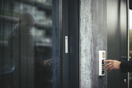 Cropped image of businessman's hand entering security code to open office door - MASF02519