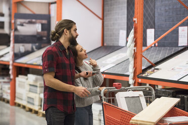Couple discussing over tiles at hardware store - MASF02525