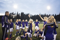 Coach standing with girls soccer team on field against sky - MASF02537