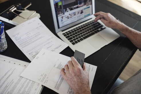 Cropped image of senior man with bills doing online payment at home - MASF02543
