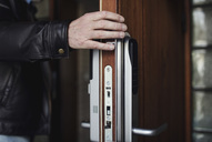 Cropped image of senior man wearing leather jacket opening wooden door - MASF02546