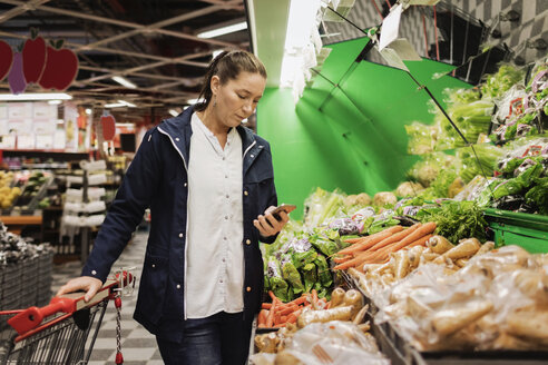 Woman using smart phone while buying groceries in supermarket - MASF02552