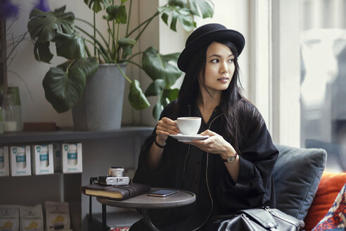 Thoughtful young woman holding coffee cup while sitting by window in creative office - MASF02555