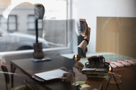 Woman taking selfie in creative office seen through glass - MASF02558
