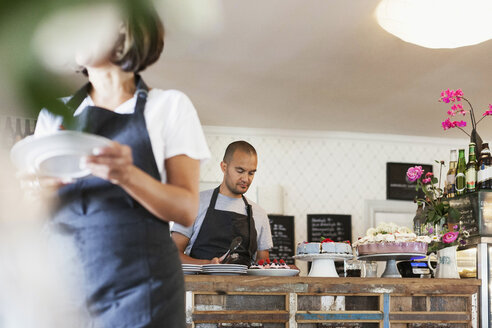 Woman holding plate and walking against male colleague working at cafe counter - MASF02561