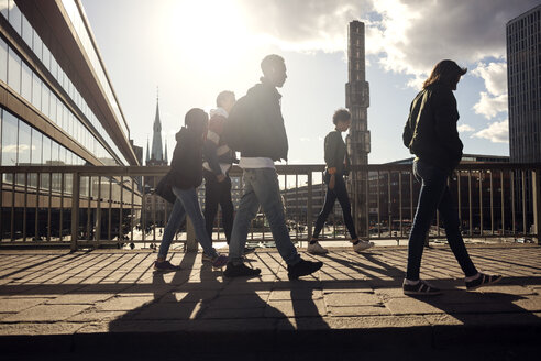 Teenagers walking on bridge by railing in city on sunny day - MASF02570