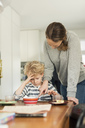 Woman and boy using digital tablet at dining table in living room - MASF02585