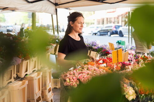 Thoughtful female owner standing at flower shop - MASF02591