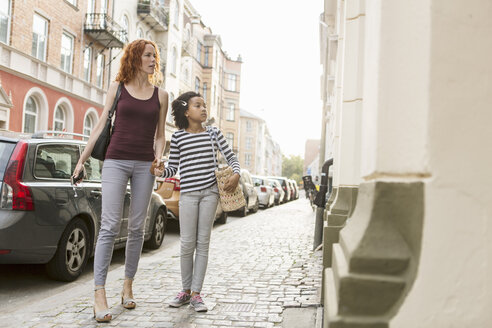 Woman walking with girl on sidewalk in city - MASF02606