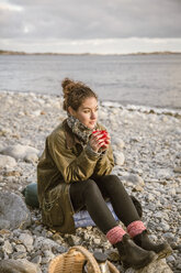 Thoughtful woman sitting on rock with drink at beach - MASF02612