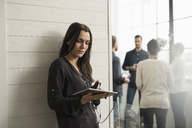 Woman holding digital tablet while leaning on wall with people in background - MASF02630