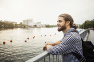 Thoughtful smiling man standing at railing by river in city against clear sky - MASF02639