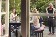 Women and teenage girl at dining table seen from window - MASF02642