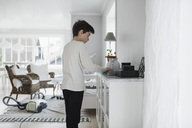 Boy cleaning cabinet in living room at home - MASF02654