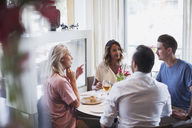 Business colleagues talking while eating lunch at restaurant during meeting - MASF02660