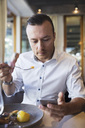 Businessman using mobile phone while eating lunch at restaurant - MASF02666