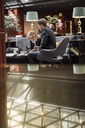 Businesswoman signing agreement by male partner sitting in hotel reception - MASF02693