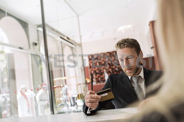 Businessman looking at credit card in hotel reception - MASF02702 - Maskot ./Westend61