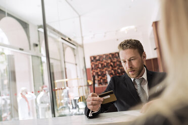 Businessman looking at credit card in hotel reception - MASF02702