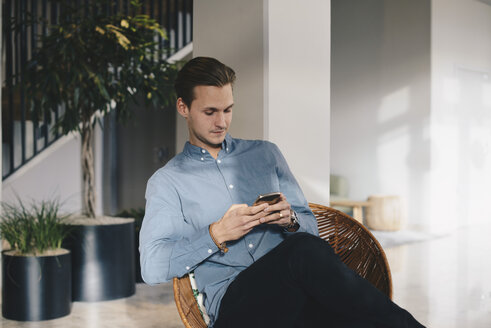 Businessman using smart phone while sitting on chair in office - MASF02705