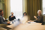 Business colleagues discussing at conference table in board room - MASF02717