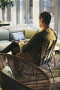 Businessman using laptop while sitting on wicker chair at office - MASF02723