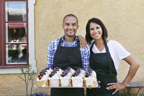 Smiling owners standing with tray of pastries outside cafe - MASF02732