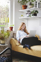 Smiling woman using laptop while resting on chaise longue at home - MASF02735