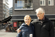 Smiling senior couple standing against building - MASF02741