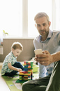 Smiling father using phone while son playing with toy blocks at home - MASF02747