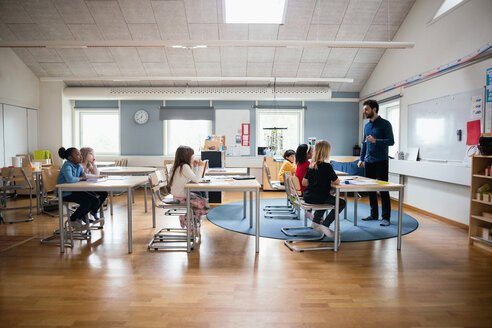 Teacher teaching students in brightly lit classroom at school - MASF02756