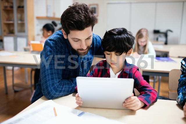 Teacher assisting male student in using digital tablet while sitting in classroom - MASF02759 - Maskot ./Westend61
